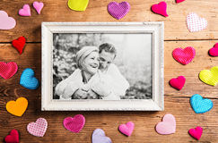 Photo of seniors in picture frame laid on wooden background. Royalty Free Stock Photos