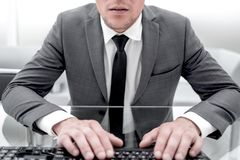 Elegant professional businessman working on computer looking at screen with hands on keyboard in office. Photo of serious ed man uses modern digital device stock image