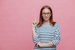 Photo of serious female shop assistant points fore finger upwards, shows blank space for your advertisement, demonstrates place royalty free stock photos