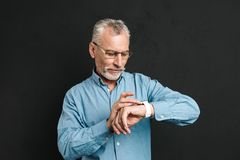 Photo of serious gentleman 60s with grey hair wearing eyeglasses. Looking at his wrist watch with tension isolated over black background Stock Photos