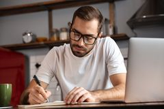 Photo of serious man writing down notes while using silver laptop on kitchen table. Photo of serious man 30s wearing eyeglasses writing down notes while using royalty free stock images