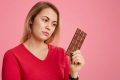 Photo of serious woman holds bar of cocoa chocolate, feels temptation, keeps to diet, dreessed in red outfit, isolated over pink. Background. People, dieting stock photos