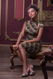 Photo session of the great model. Full-length portrait of great African model wearing lovely dress sitting on the vintage sofa in front of the wonderful wooden stock image