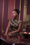 Photo session of the great model. Half-length portrait of great African model wearing lovely dress sitting in the armchair near the vintage wooden table looking stock photo
