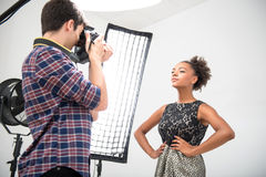 Photo session of the great model. Half-length portrait of lovely African model wearing wonderful evening dress posing in front of projectors looking at the royalty free stock photos