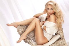 Sexy blonde woman sitting on chair, relaxing. Royalty Free Stock Photography