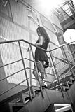 Photo of sexy brunette woman standing on metal stairs outdoor Royalty Free Stock Photos