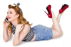 Sexy pin-up girl in shorts and high heels lying on a floor with Royalty Free Stock Image
