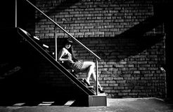 Photo of sexy woman lying on stairs at backyard of building Stock Photos