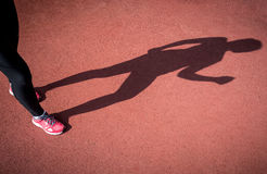 Photo of shadow of running woman on running track Stock Photo