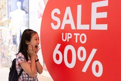 Photo shocked girl standing of shop windows with a sale,shocking price royalty free stock photos