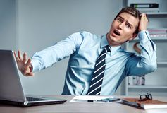 Photo of shocked man turned away from the laptop screen at the workplace. Young student in horrified. Photo of shocked man turned away from the laptop screen at stock images