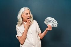 Shocked mature old woman showing money holding in hands. Photo of shocked mature old woman isolated over dark blue background. Looking aside showing money Royalty Free Stock Photos
