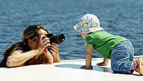 Photo Shoot. A photographer takes pictures of a one-year-old girl on the deck of a houseboat Royalty Free Stock Photo