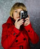 Photo shooting. Middle aged lady in red coat taking photos with vintege retro camera Royalty Free Stock Image