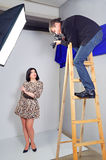 Photo shooting the model in the studio. Photographer photographing girl in the studio stock photography