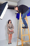 Photo shooting the model in the studio. Photographer photographing girl in the studio royalty free stock images