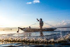 Photo shot of water spatter from fisherman while throwing fishing net on the lake. Silhouette of fisherman with fishing net in mo stock photos