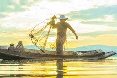 Photo shot of water spatter from fisherman while throwing fishing net on the lake. Silhouette of fisherman with fishing net in mo royalty free stock image