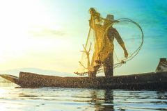 Photo shot of water spatter from fisherman while throwing fishing net on the lake. Silhouette of fisherman with fishing net in mo royalty free stock images