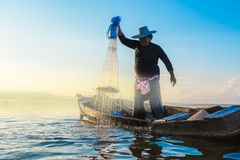 Photo shot of water spatter from fisherman while throwing fishing net on the lake. Silhouette of fisherman with fishing net in mo stock photo