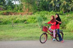 A young malay female children ride a bicycle at their hometown. Smile face from them. View a background of Malay rural village. royalty free stock images