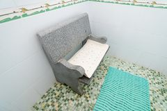 The photo of the shower room with a seat. The photo of the shower room from a tile with a seat stock images