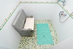 The photo of the shower room with a seat. The photo of the shower room from a tile with a seat royalty free stock photo