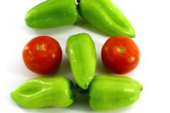 The face, composed of fresh vegetables on white background. The photo shows fresh vegetables - five sweet green peppers, two red tomatoes. Together they form the stock photos