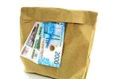 Money and paper ordinary package with products on white background. The photo shows a paper bag, universal packaging and three bills with a total amount of three stock images