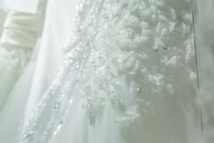 Photo shows part of the beautiful pattern of embroidered wedding dress Stock Photography