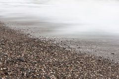 Pebbles and waves. The photo shows the pebbles and waves Royalty Free Stock Images