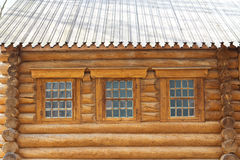 The photo shows the wall of a wooden house with windows Stock Photos