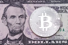 Photo of silver bitcoin on dollar banknote background. Royalty Free Stock Images