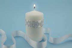 Photo of single white lit candle isolated with white satin ribbo Stock Photo