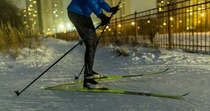 Photo of skier in park in background of house, burning lights. On winter evening Stock Photo