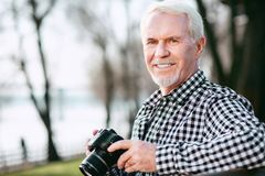 Optimistic mature man challenging with photography Royalty Free Stock Photography