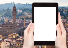 Photo of skyline of Florence with Palazzo. Travel concept - tourist photographs skyline of Florence city with Palazzo Vecchio on tablet with cut out screen with Stock Images