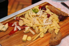 Photo sliced and ready to eat variety of foods: different kinds of cheese, cured ham, smoked sausage, grapes and bread Royalty Free Stock Photography
