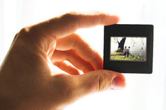 Photo slide. Hand and slide. Old color slide against light Stock Photography