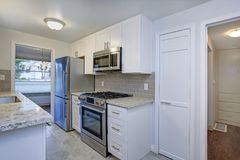 Photo of a small compact kitchen with white shaker cabinets. Topped with quartz counter tops, subway tile and stainless appliances stock photos