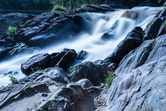The photo of small waterfall or cataract in the forest taked in the warm sunny summer day with the long exposure. The stream of the brook is flowing among the royalty free stock photo