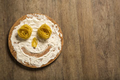 Photo of smiling faces from pasta and flour lying on a wooden ta Stock Photos