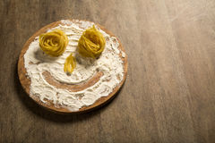 Photo of smiling faces from pasta and flour lying on a wooden ta Royalty Free Stock Image