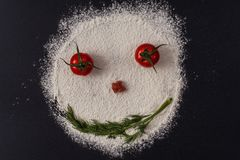 Photo of smiling faces from tomato parsley flour lying on a black. Concept Royalty Free Stock Photography