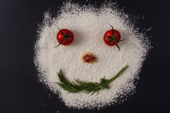 Photo of smiling faces from tomato parsley flour lying on a black. Concept Stock Photos