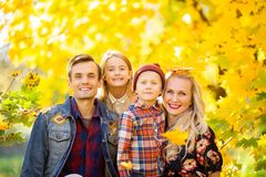 Photo of smiling family with son and daughter on walk in autumn park stock images