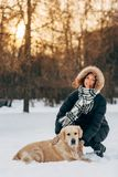 Photo of smiling girl on walk with dog on background of trees. In winter park at afternoon Stock Image
