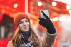 Photo smiling girl in warm clothes and hat taking selfie on yaskravnomu red urban background stock photography