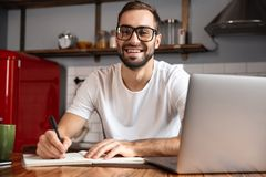 Photo of smiling man writing down notes while using silver laptop on kitchen table. Photo of smiling man 30s wearing eyeglasses writing down notes while using royalty free stock photography
